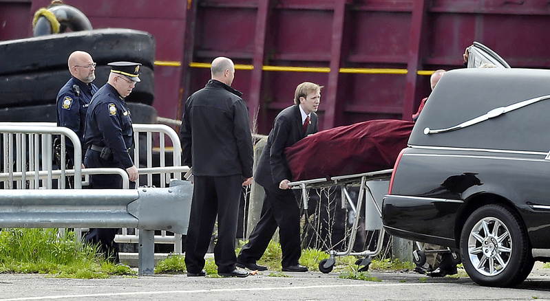 The body of Nathan Bihlmaier is lifted into the waiting hearse at a restricted portion of the Maine State Pier on Tuesday. The hearse took his body to Augusta for an autopsy.