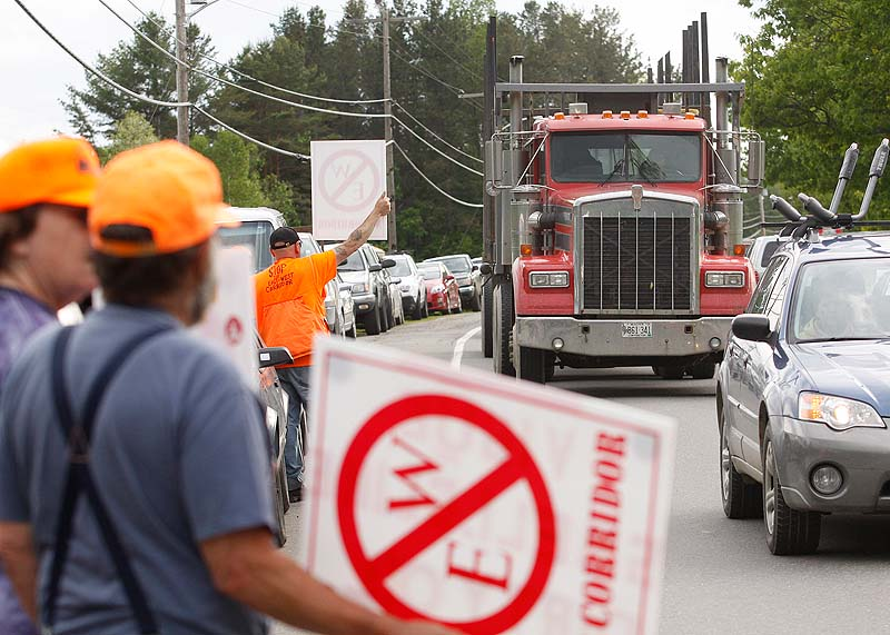 Protesters hold up signs up toward oncoming traffic before a public meeting in Dover-Foxcroft concerning the proposed East-West Highway.
