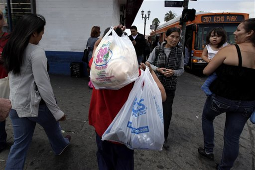 A boy carries plastic bags as he crosses a street in Los Angeles, Thursday, May 24, 2012. Now that the city of Los Angeles has taken the first step toward banning plastic bags, it appears the little utilitarian bags themselves may be headed for the trash heap of history. (AP Photo/Jae C. Hong)