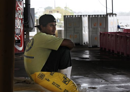 In this May 16, 2012, photo, dock worker Edwin Gomez sits on an empty dock at Ken Lee's Dock in Lafitte, La. The mood is gloomy on the hard-working shrimp and crab docks of this gritty fishing town in the Barataria estuary, a traditional seafood basket for New Orleans, as the second full year of fishing since BP�s catastrophic oil spill kicks into high gear. Usually folks are upbeat and busy in May, the month when shrimpers get back to work in Louisiana�s rich waters. But this spring, catches are down, docks are idle and anxiety is growing that the ill effects of the BP spill may be far from over. (AP Photo/Gerald Herbert)