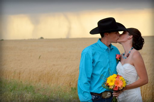 In this May 19, 2012, photo provided by Cate Eighmey, Caleb & Candra Pence pose for a wedding photo as a tornado swirls in the background after they were married in Harper County, Kan. (AP Photo/Cate Eighmey) MANDATORY CREDIT