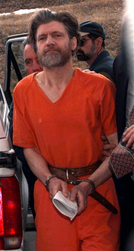 FILE - In this April 4, 1996 file photo, Ted Kaczynski, also known as the Unabomber, is escorted into the federal courthouse in Helena, Mont. Harvard alumni attending their 50th class reunion are getting updates on classmates _ including Kaczynski, who graduated in 1962. In an alumni directory, he lists his occupation as �prisoner� and under awards lists �eight life sentences.�(AP Photo/Elaine Thompson, File)