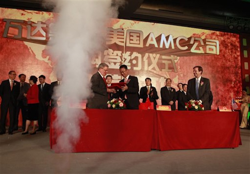 Gerry Lopez, CEO of AMC Entertainment Holdings, center left, exchanges documents with Zhang Lin, vice president of Wanda during a signing ceremony for Dalian Wanda Group Co. to acquire AMC Entertainment Holdings in Beijing, China, Monday, May 21, 2012. The Chinese conglomerate announced Monday it will buy major U.S. cinema chain, AMC Entertainment Holdings, for $2.6 billion to create the world's biggest movie theater operator. Looking on at right is Eliot Merrill, representative of AMC shareholders. (AP Photo/Ng Han Guan)