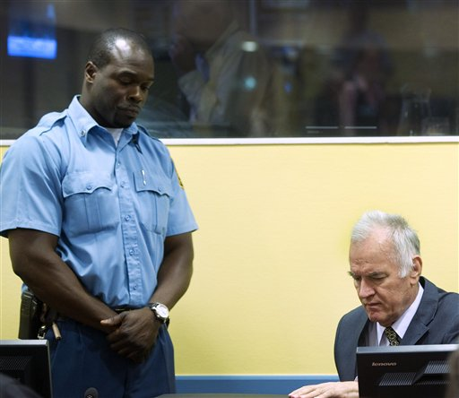Former Bosnian Serb military commander Gen. Ratko Mladic, right, and a UN security guard are seen at the start of his trial at the Yugoslav war crimes tribunal in The Hague, Netherlands, today.