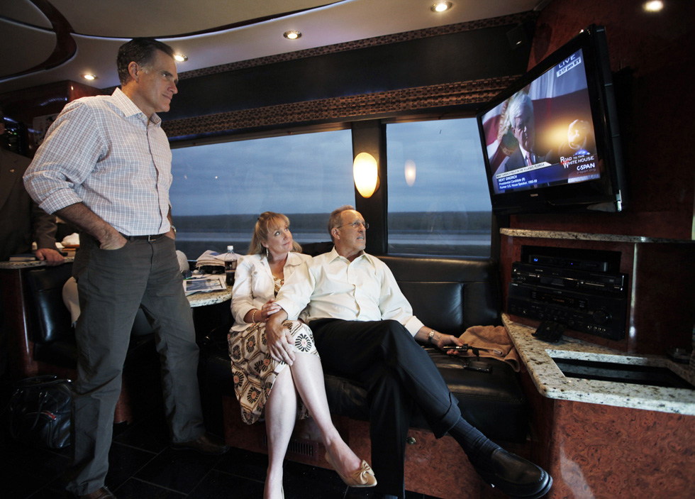 In this Jan. 29, 2012, photo, Republican presidential candidate Gov. Mitt Romney, left, watches Republican presidential candidate Newt Gingrich on television as he rides his Florida campaign bus with his brother Scott, and sister-in-law Sheri, to Hialeah, Fla.
