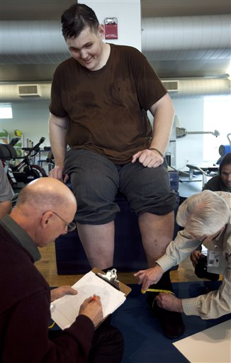 Igor Vovkovinskiy, of Minneapolis, currently the tallest man in the United States, has his feet measured by shoe technicians as part of a shoe fitting at Reebok headquarters in Canton, Mass., today.