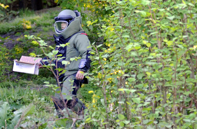 BOMB SEARCH: Maine State Police Sgt. Jeff Mills carries material to detonate Thursday outside an apartment building on Gage Street in Augusta. Law enforcement officers from several agencies searched two apartment buildings on the street for explosive materials. The State Police Bombs Team exploded material located in an apartment on Gage Street in the yard behind behind it.