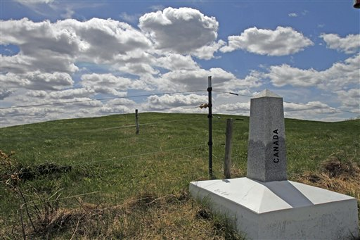 A marker in Stanstead, Quebec, locates the border in front of the proposed site of a U.S. wind turbine project in Derby Line, Vt.