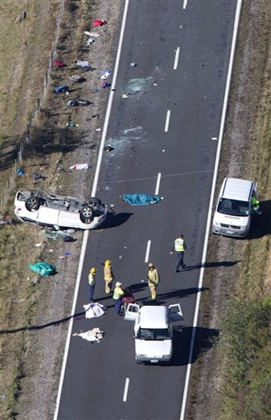 Police and fire crew examine the scene of a minivan crash near Turangi, New Zealand, Saturday, May 12, 2012. Three Boston University students who were studying in New Zealand were killed Saturday when their minivan crashed. At least five other students from the university were injured in the accident, including one who was in critical condition. (AP Photo/New Zealand Herald, John Cowpland)