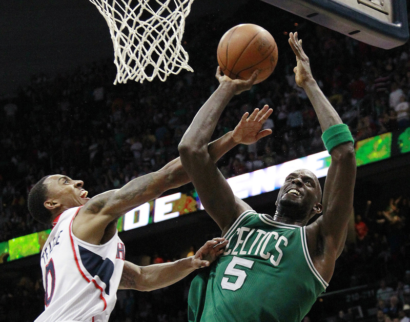 Boston Celtics' Kevin Garnett pulls down a rebound as Atlanta Hawks guard Jeff Teague defends in the second half of Game 2 of the first-round playoff basketball series Tuesday in Atlanta. Boston won 87-80 and evened the series at one game each.