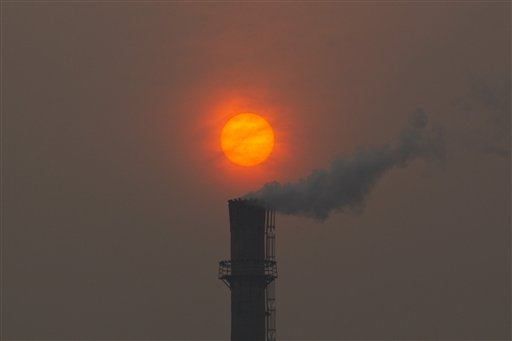 Smoke billows from a chimney of a heating plant as the sun sets in Beijing in this Feb. 13, 2012 photo. Scientists say carbon emissions from fast-growing economies like China and India as well as developed industrialized nations tare overheating the planet.