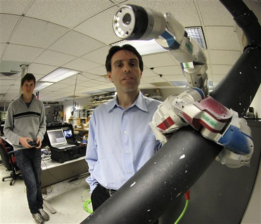 Carnegie Mellon University Professor Howie Choset, right, watches a robot as staff researcher Florinan Enner uses a controller to demonstrate how it climbs up a tubular armature at their lab on campus in Pittsburgh.
