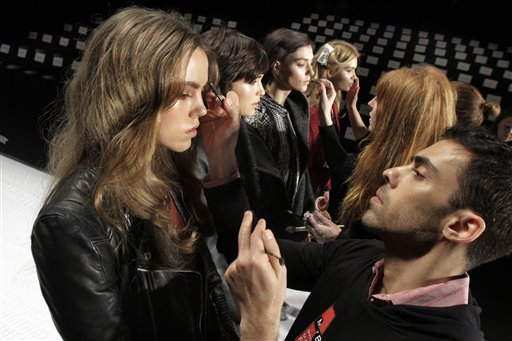 Models have their make-up finalized under runway light during Fashion Week in New York recently. The 19 editors of Vogue magazines around the world made a pact to project the image of healthy models.