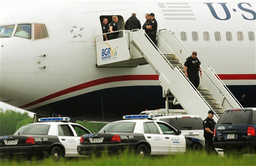 Law enforcement officials stand on a jet bridge and a passenger jet on the tarmac at Bangor International Airport, in Bangor, Me., Tuesday, May 22, 2012. The plane was diverted to Maine during its flight from France to Charlotte. Officials briefed on the incident say a French passenger passed a note to a flight attendant saying she had a surgically implanted device. (AP Photo/Bangor Daily News, Kevin Bennett)
