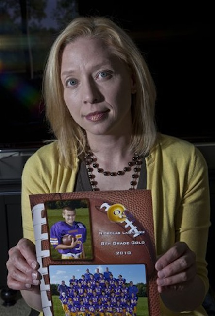 Kia LaBracke holds up a picture of her son in her home Friday, May 18, 2012, in Oconomowoc, Wis. LaBracke is concerned about her kids playing football in the wake of NFL concussions. (AP Photo/Morry Gash)