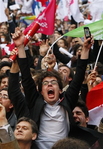 A supporter of Socialist Party candidate for the presidential election Francois Hollande reacts after the first results of the second round of French presidential elections outside Socialist Party campaign headquarters in Paris, France, Sunday, May 6, 2012. First results show that Hollande had won the election. (AP Photo/Francois Mori)