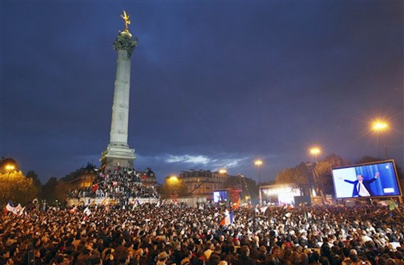 Supporters of Socialist President-elect Francois Hollande, seen on the video screen at right, celebrate after the results of the second round of the French Presidential elections were announced at Bastille square in Paris, France, Sunday, May 6, 2012. Hollande defeated outgoing President Nicolas Sarkozy on Sunday to become France's next president, Sarkozy conceded defeat minutes after the polls closed. (AP Photo/Francois Mori)