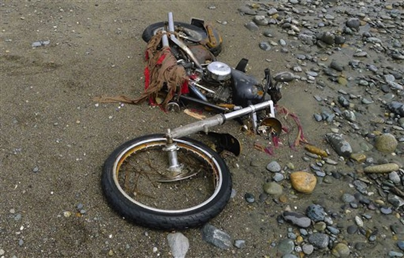 In this photo taken by Canadian Peter Mark in the end of April 2012, and released on Wednesday, May 2, a Harley-Davidson motorbike lies on a beach in Graham Island, western Canada. Japanese media say the motorcycle lost in last year's tsunami washed up on the island about 6,400 kilometers (4,000 miles) away. The rusted bike was originally found by Mark in a large white container where its owner, Ikuo Yokoyama, had kept it. The container was later washed away, leaving the motorbike half-buried in the sand. Yokoyama, who lost three members of his family in the March 11, 2011, tsunami, was located through the license plate number, Fuji TV reported Wednesday. (AP Photo/Kyodo News, Peter Mark)