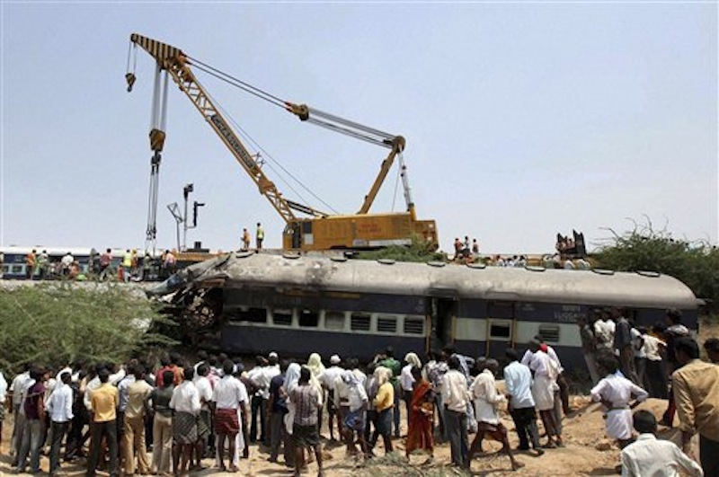 People watch rescue work at the scene of a train accident at a station near Penukonda, about 170 kilometers (105 miles) north of Bangalore, India, Tuesday, May 22, 2012. The passenger train rammed into a parked freight train and burst into flames before dawn Tuesday, killing more than a dozen people in southern India, officials said. (AP Photo)