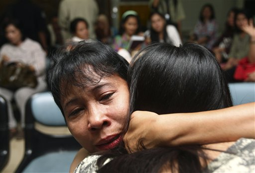 A relative weeps as she and others wait for the latest news on the Russian passenger jet that crashed into a steep cliff on a long-dormant Indonesian volcano on Wednesday, at Halim Perdanakusuma Airport in Jakarta, Indonesia, today.