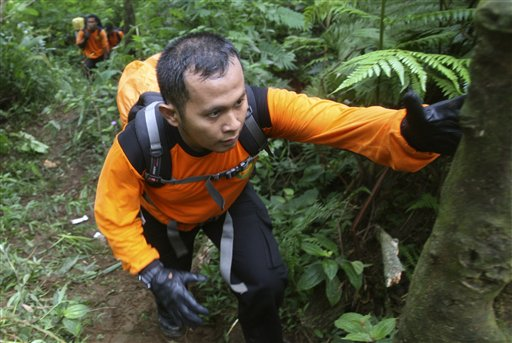 Indonesian rescuers walk through rugged terrain as they make their way to the site of a plane crash at Salak mountain in Cijeruk, Bogor, West Java, Indonesia, today. All on board were feared dead.