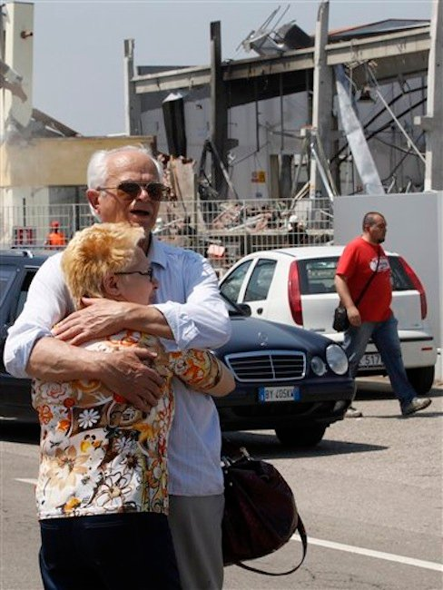 Mr. Borghi who lost his son in the building embraces his wife in front of the destroyed BBG industrial moldings in Mirandola, northern Italy, Tuesday, May 29, 2012. A magnitude 5.8 earthquake struck northern Italy on Tuesday, killing at least 10 people as factories, warehouses and a church collapsed in the same region still struggling to recover from another deadly tremor nine days ago. (AP Photo/Luca Bruno)