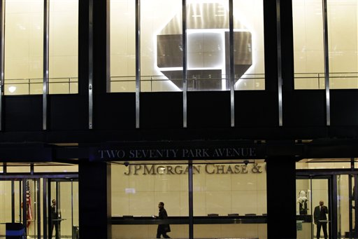 People walk inside the lobby of a JPMorgan Chase building in New York on Thursday. The company's stock plunged almost 7 percent in after-hours trading after the loss was announced. Other bank stocks, including Citigroup and Bank of America, suffered heavy losses as well.
