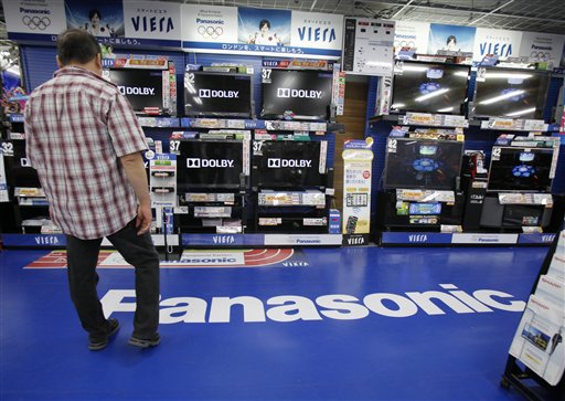 A man looks at a line of Panasonic TV products at an electric store in Tokyo today. Panasonic Corp.'s January-March losses ballooned 10-fold, completing a year of record red ink at the Japanese electronics maker battered by natural disasters and an ailing TV business.
