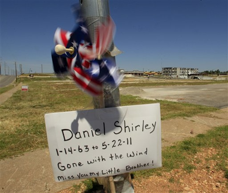 A sign remembering a tornado victim is seen on a street corner Tuesday, May 22, 2012, in Joplin, Mo. The community is marking the anniversary of an EF-5 tornado that killed 161 people as it cut a wide swath through Joplin a year ago. (AP Photo/Charlie Riedel)