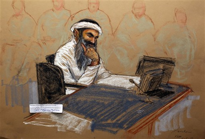 In this photo of a sketch by courtroom artist Janet Hamlin and reviewed by the U.S. Department of Defense, Khalid Sheikh Mohammed reads a document during his military hearing at the Guantanamo Bay U.S. Naval Base in Cuba, Saturday, May 5, 2012. The self-proclaimed mastermind of the Sept. 11 attacks repeatedly declined to respond to a judge's questions Saturday and his co-defendant was briefly restrained at a military hearing as five men charged with the worst terror attack in U.S. history appeared in public for the first time in more than three years. (AP Photo/Janet Hamlin, Pool)
