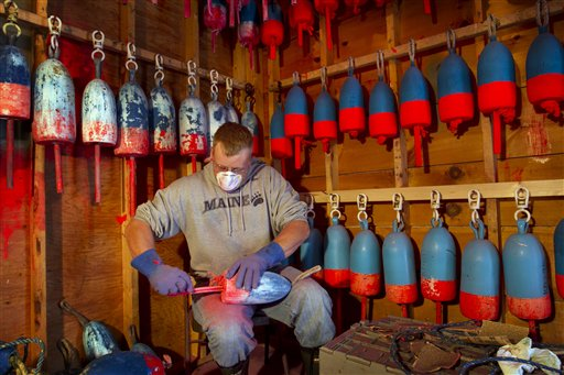 Lobsterman Kendall Delano sands last year's paint off lobster buoys he's painting in his workshop in Friendship on Thursday.
