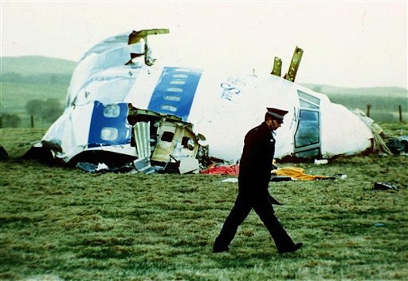 A police officer walks by the nose of Pan Am flight 103 in a field near the town of Lockerbie, Scotland where it lay after a bomb aboard exploded, killing a total of 270 people, in this December 21, 1988 file photo. The son of the former Libyan intelligence officer convicted of the bombing says his father has died. Abdel Baset al-Megrahi was released in 2009 from his Scottish prison on humanitarian grounds. Al-Megrahi suffered from prostate cancer. His death was announced on Sunday May 20 2012 by his son, Khaled. (AP Photo/Martin Cleaver, File)