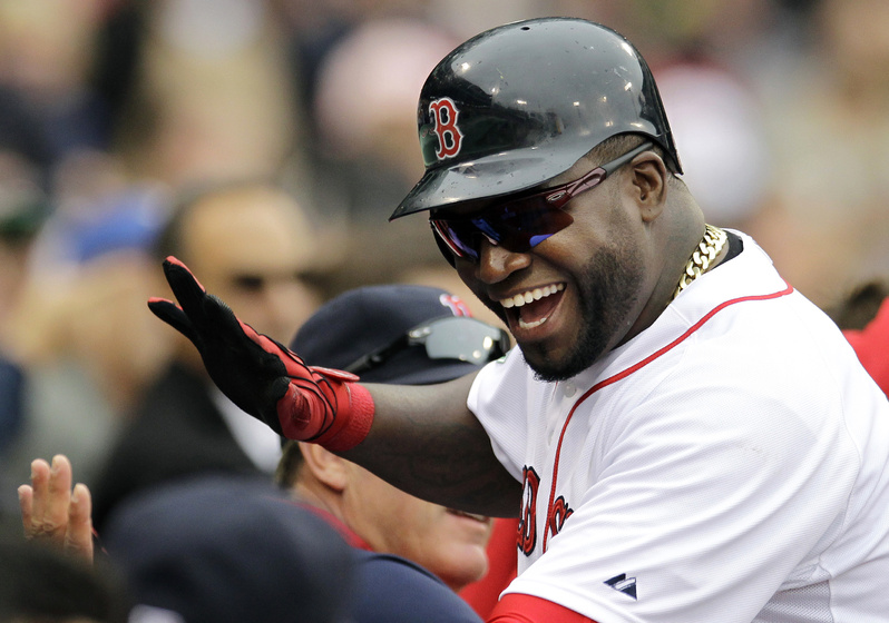 Boston Red Sox designated hitter David Ortiz celebrates as he returns to the dugout after scoring on a single by Will Middlebrooks in the fifth inning against the Seattle Mariners at Fenway Park in Boston today. Boston won 5-0.