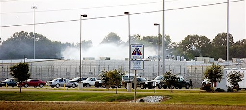 Smoke rises above the Adams County Correctional Center in Natchez, Miss., Sunday, May 20, 201, during an inmate disturbance at the prison. A guard at the southwest Mississippi prison died Sunday and several other employees were injured during what the facility's private operator is calling