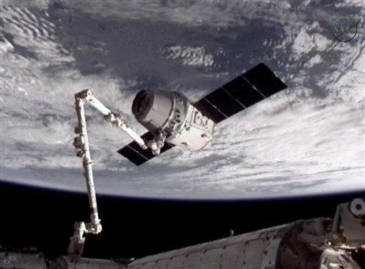 This image provided by NASA-TV shows the SpaceX Dragon commercial cargo craft, top, after Dragon was grappled by the Canadarm2 robotic arm and connected to the International Space Station, Friday, May 25, 2012. Dragon is scheduled to spend about a week docked with the station before returning to Earth on May 31 for retrieval. (AP Photo/NASA)