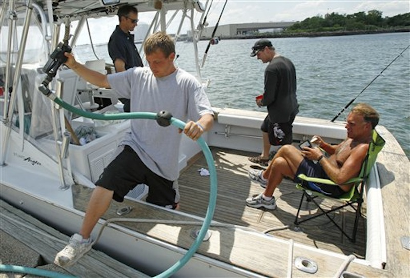 In this June 29, 2011 photo, fuel attendant Derek Locke, of Lynn, Mass., steps out of a sports fishing boat while fueling up on board as Ryan Chasse, of Lynn, opens his wallet to pay at the Seaport Landing Marina in Lynn, Mass. Much remains unknown about the region's hundreds of thousands of recreational boaters, even though they've been enjoying the chilly ocean waters as long as there have been people on land. Now, a massive survey aims to find out more about what these boaters do. (AP Photo/Charles Krupa)