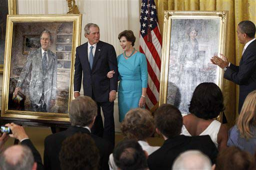 President Barack Obama applauds as former President George W. Bush and former first lady Laura Bush stand during the unveiling of their official portraits today.