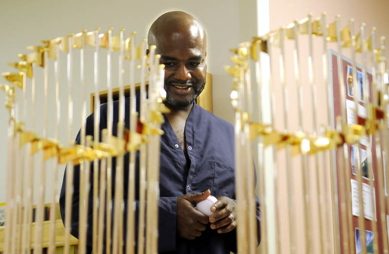 Clutching a baseball he received from the Fenway Ambassadors, VA Maine Healthcare System-Togus patient Robert Johnson Jr., of Searsport, inspects the Red Sox World Series trophies on display Wednesday at the hospital for veterans.
