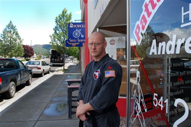 Andrew Lee Patterson stands Thursday, May 24, 2012 outside his karate studio in Gold Hill, Ore. Patterson says he no longer wants to be known for the violence and white supremacist beliefs that sent him to prison and led him to lead a chapter of the neo-Nazi National Socialist Movement. But a city councilor in Gold Hill wants people to know about his past before deciding to entrust their children to his teaching. (AP Photo/Jeff Barnard)