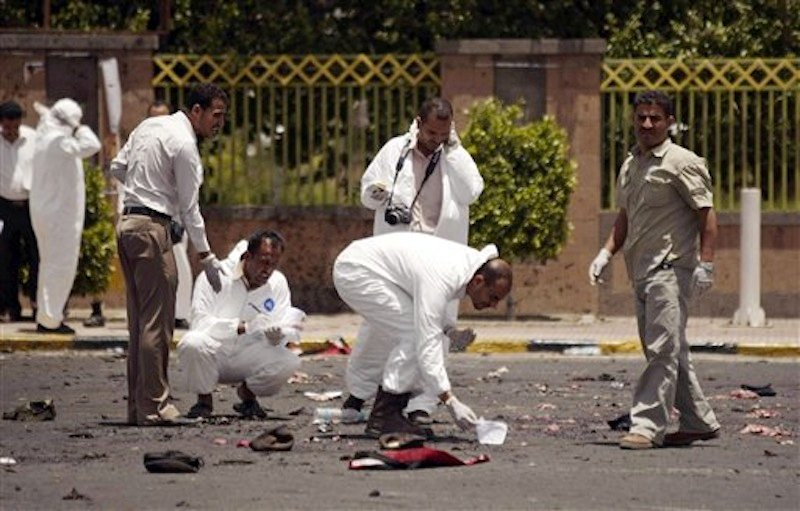 Forensic policemen collect evidence at the site of a suicide bomb attack at a parade square, killing some scores of people, in Sanaa, Yemen, Monday, May 21, 2012. Officials say Monday's bombing near Sanaa's presidential palace is one of the deadliest attacks in the city in months. (AP Photo/Hani Mohammed)