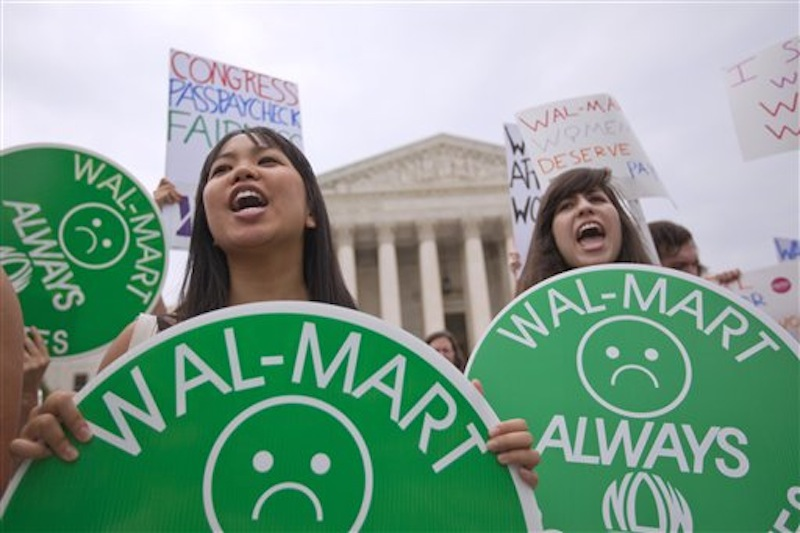 In this Tuesday, June 21, 2011 file photo, demonstrators hold signs outside the Supreme Court in Washington to protest the court's Wal-Mart sex discrimination class action lawsuit decision. For years, the world's largest retailer has tried to repair a reputation that's been damaged by decades of criticism and legal troubles. In April 2012, allegations that Wal-Mart paid bribes to officials in Mexico threaten to derail Wal-Mart's attempts to improve its image. (AP Photo/Evan Vucci)