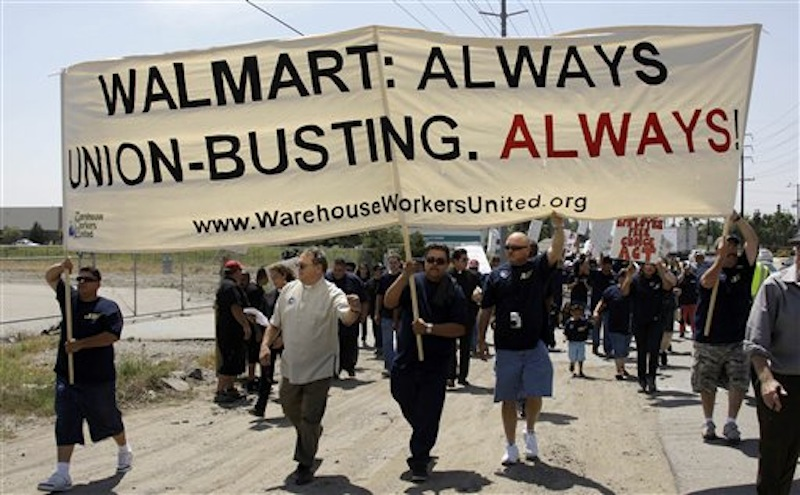 In this Thursday, May 14, 2009 file photo, about 100 demonstrators march down a highway as union organizers, clergy, students and others demonstrate at a Wal-Mart distribution center in Fontana, Calif. For years, the world's largest retailer has tried to repair a reputation that's been damaged by decades of criticism and legal troubles. In April 2012, allegations that Wal-Mart paid bribes to officials in Mexico threaten to derail Wal-Mart's attempts to improve its image. (AP Photo/Reed Saxon)