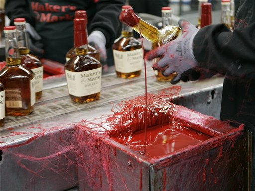 A bottle of Maker's Mark bourbon is dipped in red wax during a tour of the distillery in Loretto, Ky., recently.
