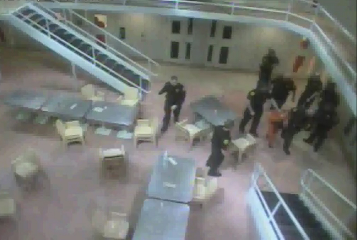 A screen image from a video provided by the Maine ACLU that purportedly shows Wilmer Moreno Recinos being led away after being beaten by Cumberland County jail guards.