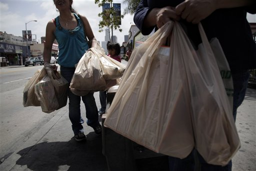 Two women wait for a bus after their grocery shopping in Los Angeles, Thursday, May 24, 2012. Now that the city of Los Angeles has taken the first step toward banning plastic bags, it appears the little utilitarian bags themselves may be headed for the trash heap of history. (AP Photo/Jae C. Hong)