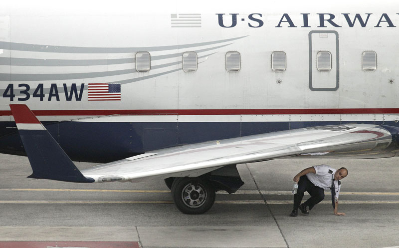 A member of the flight crew on U.S., Airways commuter jet, tail number N434AW, completes a walk-around of the aircraft at Logan International Airport in Boston, yesterday. A man has been arrested in Boston after allegedly trying to open a cabin door of the jet flying from Maine to Philadelphia.