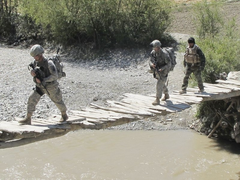 Soldiers from Bravo Company's 1st Platoon and a member of the Afghan Border Police cross a bridge near Meydani, Afghanistan, in 2010.