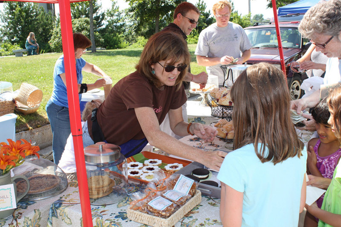 Paula Costin of Sugar Hill Baking serves a long line of customers at the South Portland Farmers' Market last July.