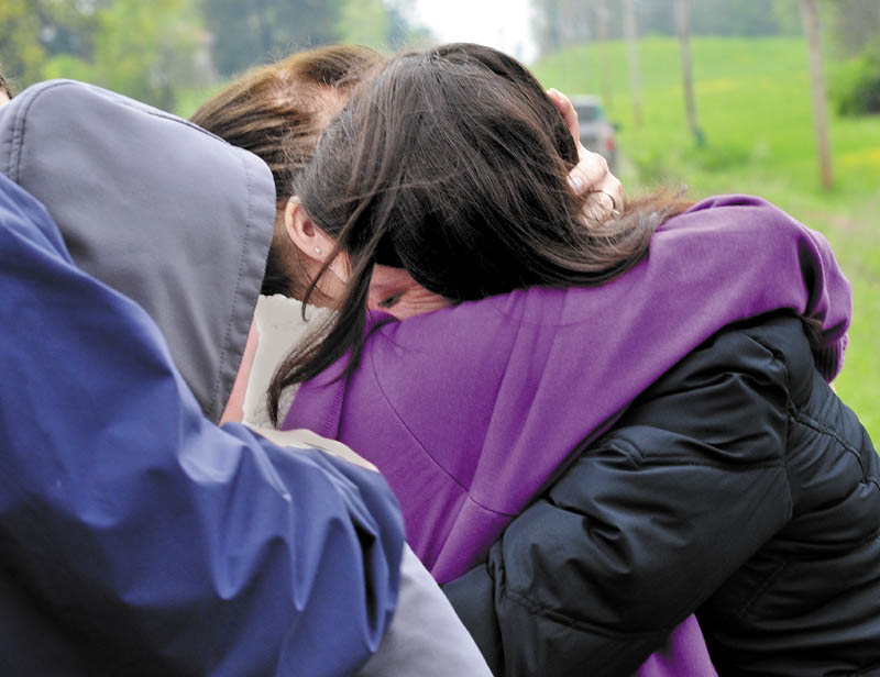 COMFORT: Paula Berry, right, daughter of missing driver Cora Marley, hugs Marley's twin sister Dora Gagnon in Hinckley on Tuesday where an extensive search is underway for Marley who crashed into a bridge over Martin Stream last Saturday.
