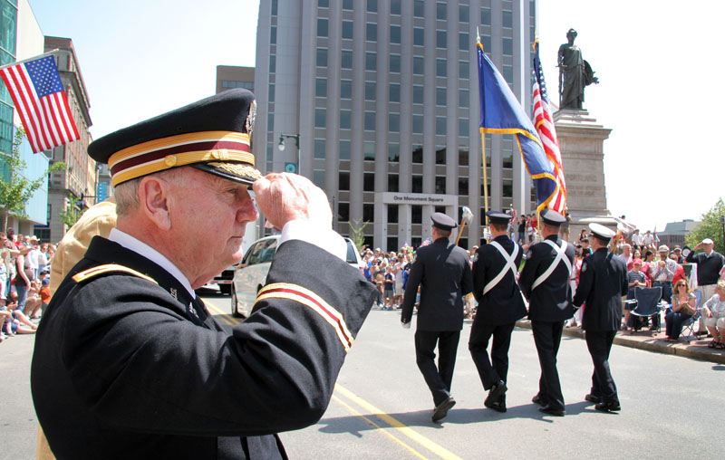 Col. Arthur Wickham of Windham, U.S. army retired, salutes as the Portland color guard passes by along Congress Street during the Portland Memorial Day parade today.